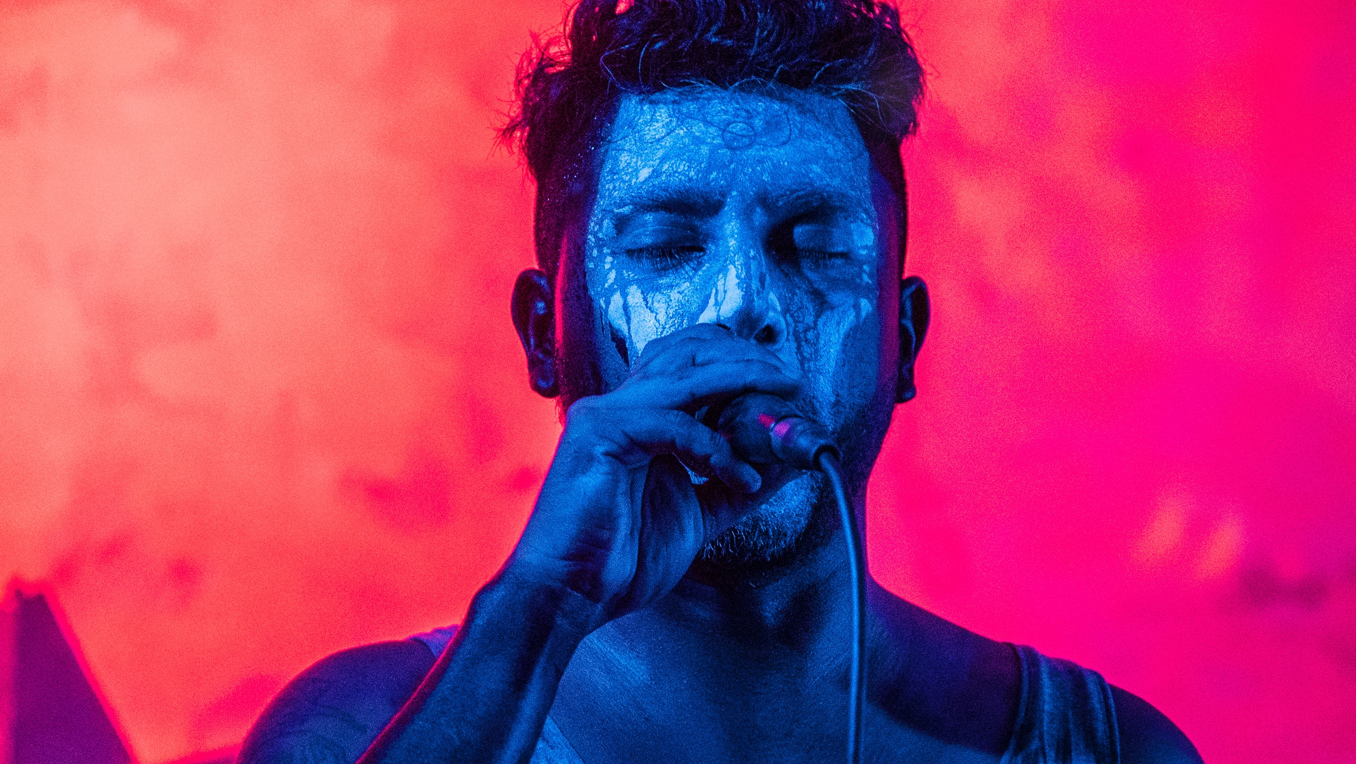 Male singer, blue lighting, red background | Elise Franklin Therapy & Coaching | Entertainment Industry Counseling | Therapy for Bands, Musicians, Artists, Actors & Performers | Los Angeles, CA 90064 | Los Angeles, CA 90017